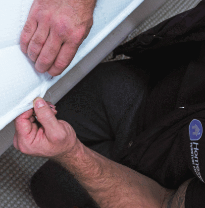 Technician in the process of checking the mattress for any defects